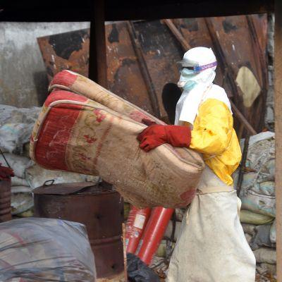 En hjälparbetare i skyddsutrustning flyttar en madrass i Guinea i december ifjol.