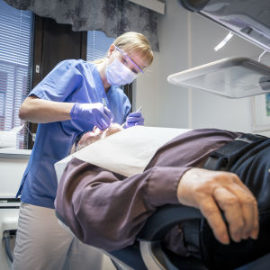 Tandläkare kollar tänderna på en patient