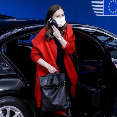 Sanna Marin i munskydd talar i telefon och stiger ur en bil.