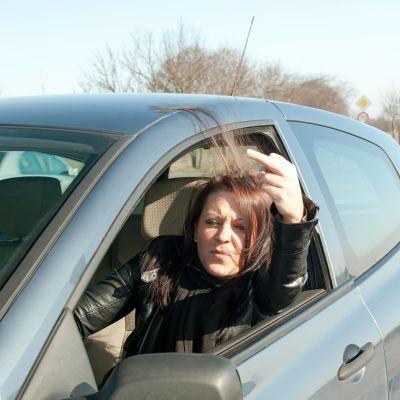 Kvinna i bil visar långfingret.