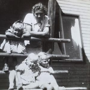 Äiti ja kolme tytärtä talon rappusilla. Kaksi tytöistä istuu ja pienin tytöistä seisoo äidin vieressä kaiteeseen nojaten,