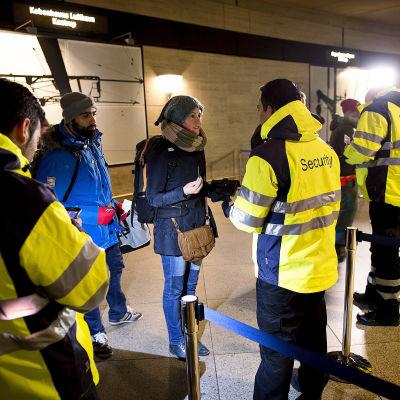 Säkerhetspersonal kontrollerar människors personhandlingar vid Kastrup tågstation.
