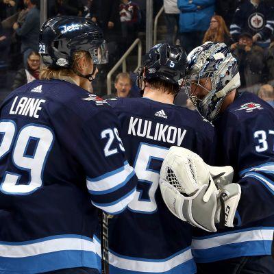 Dmitry Kulikov ja Patrik Laine onnittelevat maalivahti  Connor Hellebuyckia voitokkaan pelin jälkeen.