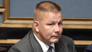 Riksdagsman Juha Mäenpää på sin plats i riksdagen.