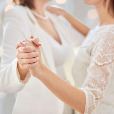 Kvinnligt par i brudklänning dansar i sidoprofil.
