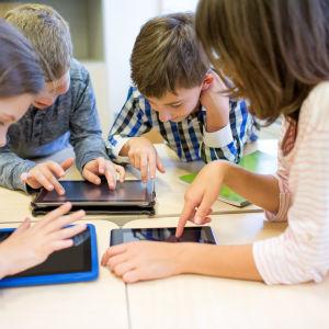 Fyra barn står lutade över bord och använder pekplattor.