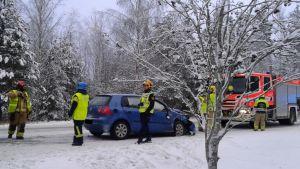 Brandmän står vid bil som har plåtskador.