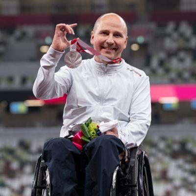 Toni Piispanen håller upp sin silvermedalj.