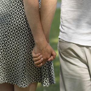 Mies ja nainen pitävät toisiaan kädestä