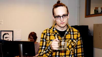 Axel Åhman håller en mugg i handen.