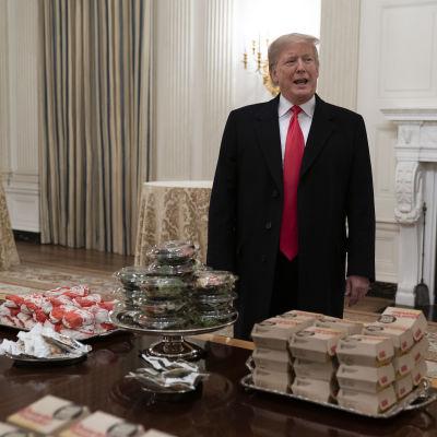 Preisdent Trump bakom ett bord fullt av hamburgare som serverades åt fotbollslaget Clemson Tigers i Vita huset