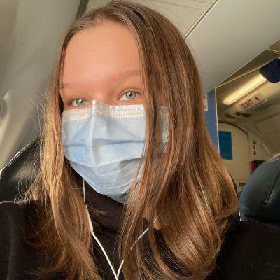 Tinka Pelttari lentokoneessa maski kasvoilla.