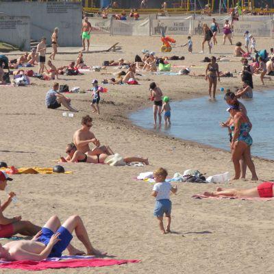 Paljon uima-asuisia ihmisiä hiekkarannalla ja rantavedessä.