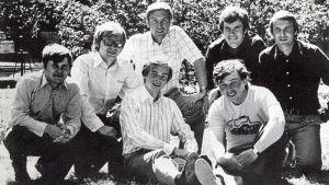 Svensk Ungdoms kandidater i riksdagsvalet 1975 poserar i solsken på en gräsmatta. Nere i mitten: Michael Franck och Hans Invesgård, övriga fr v.: Christoffer Taxell, Björn Månsson, Pär Stenbäck, Per-Håkan Slotte och Håkan Nordman.