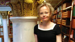 En kvinna iklädd en svart klänning. Står och lutar sig mot ett räcke. Det ser ut som att hon befinner sig i ett bibliotek.