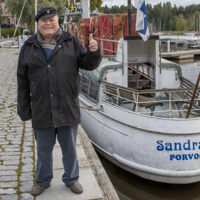 Skeppare Ari Kautto visar tummen upp där han står intill fartyget Sandra D.