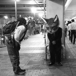 Nuori nainen ja kissapäinen mies tervehtivät toisiaan japanilaisella asemalla. Kuva elokuvasta Terveisiä Fukushimasta.