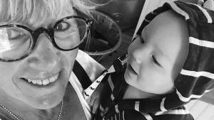 Anna Gullichsen med barnbarnet som är en bebis i famnen.