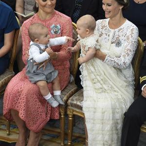 Kusinerna prins Oscar och prins Alexander hälsar på varandra i famnen på sina mammor.