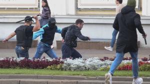 Två batongbeväpnade män jagar en en tredje man.