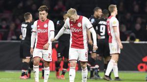 Två Ajaxspelare går och stirrar ner mot gräset.
