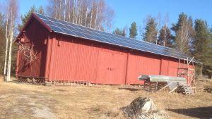 En röd lada med solpaneler på taket.