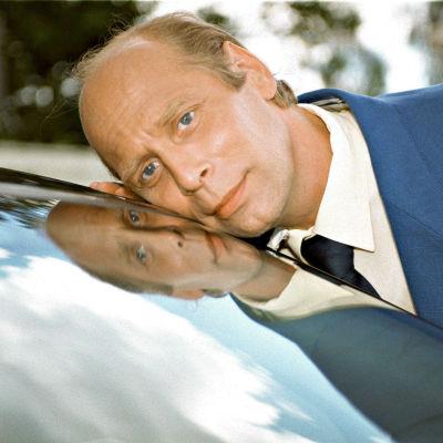 Mies (Vesa Vierikko) nojaa poskeaan auton tuulilasia vasten.