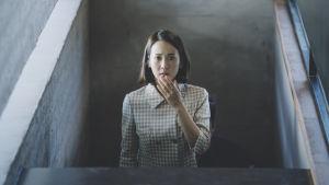 Park Yeon-kyo (Yeo-jeong Jo) står i en trappa och ser förskräckt ut.