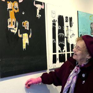 vanha nainen katsoo maalausta