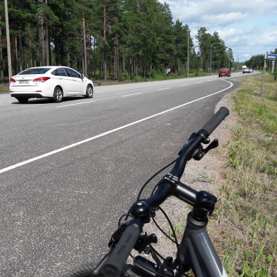 Bilar kör på en riksväg. I förgrunden syns ett cykelstyre.