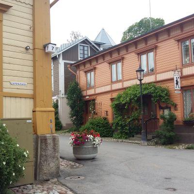 Trähus och en skylt som pekar mot Mannerheiminkatus butiker i Nådendal.