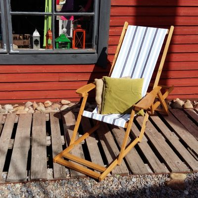 En solstol med tygsits som står på en altan utanför en röd stuga.
