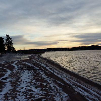 Ispois simstrand på vintern, med snö och is på stranden, men ingen is på Långvattnet.