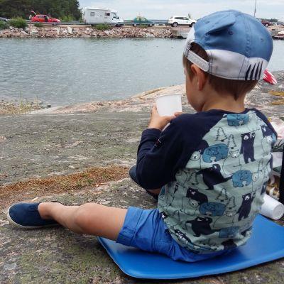 En liten pojke med blå kläder och blå skärmmössa leker vid stranden med en vit platsmugg, medan en lång rad bilar i bakgrunden väntar på färjan.