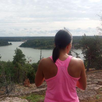 En dam i rosa topp tittar ut från en bergstopp över öar och skärgård.