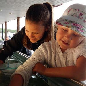 Wilma Johansson, en dam med mörk hästsvans, och Nellie Walldén, en flicka med vit keps, sträcker ner varsin hand i ett stort akvarium för att putsa av det.
