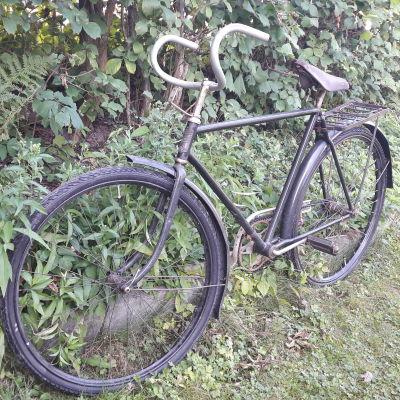 En gammal cykel av modellen Felix Special står vid en häck.
