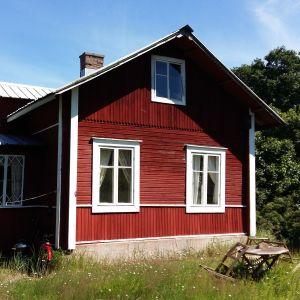 Röd stuga med vita knutar i sommargrönska på Berghamn i Houtskär.