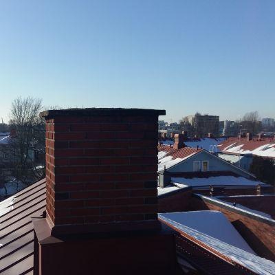 En skorsten på ett snöigt tak i trähusstadsdelen Port Arthur i Åbo.