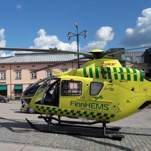 En gul räddningshelikopter står på ett torg.