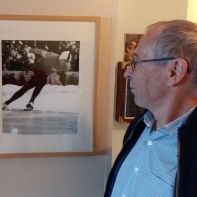 Hastighetsåkaren Olavi Hjellman tittar på tavlor av sig själv från en skridskotävling och av diplomet från vinter-OS 1968 i Grenoble.