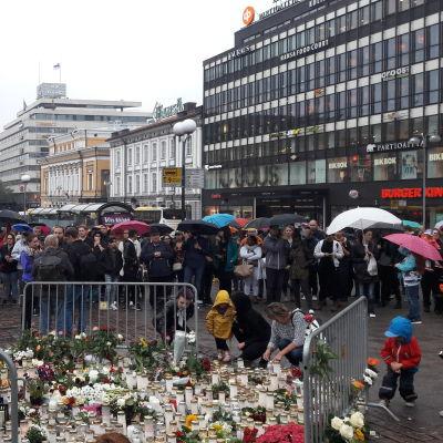 Människor samlas kring blommor och ljus på Åbo torg.