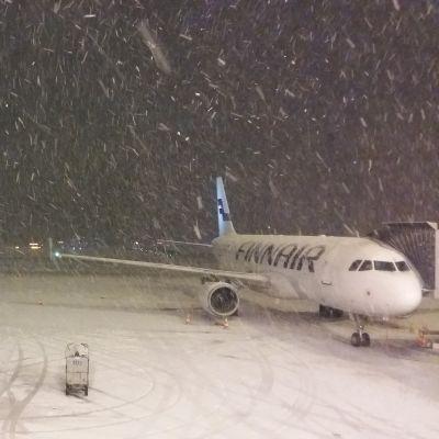 Ett Finnairplan väntar i snöyra på att börja ta emot passagerare.
