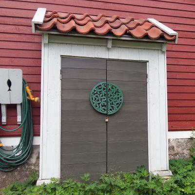 Ett litet förråd byggt mot en husfasad.