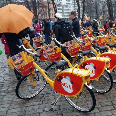 Ett 50-tal lånecyklar är parkerade på Domkyrkotorget i Åbo. Folk står med paraplyer och väntar på att få börja använda dem.