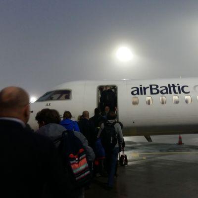 Passagerare vandrar ombord på ett AirBaltic-plan i dimma.