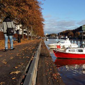 En man går förbi en knallröd båt i Aura å en solig höstdag i Åbo.