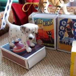 Små miniatyraffischer med vintagebilder klistrade på tändsticksaskar, en liten leksakshund av plast och en träkloss.