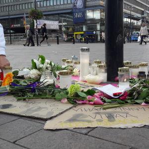 Blommor och ljus placeras vid platsen där offret misshandlades.