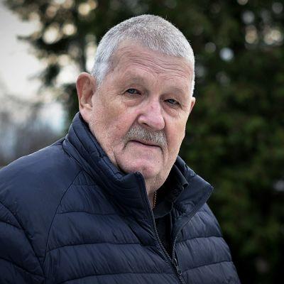 En äldre man står utomhus i novembermiljö och ser rakt in i kameran.